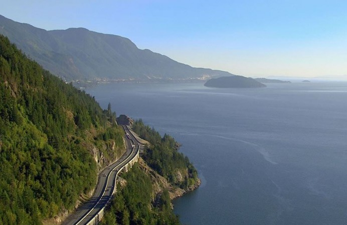 Cars-driving-the-Sea-to-Sky-Highway-between-Vancouver-and-Whistler-with-ocean-and-mountains-in-the-background-CR