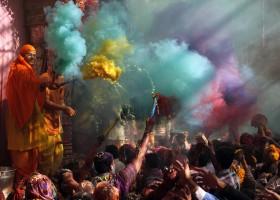 Hindu priests throws coloured powder at the devotees during Holi celebrations at Bankey Bihari temple in Vrindavan