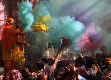 Hindu priests throws coloured powder at the devotees during Holi celebrations at Bankey Bihari temple in Vrindavan